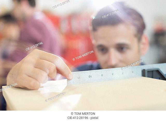 Close up carpenter measuring wood with ruler