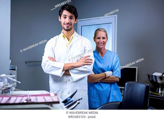 Portrait of smiling dentist and dental assistant standing with their hands crossed
