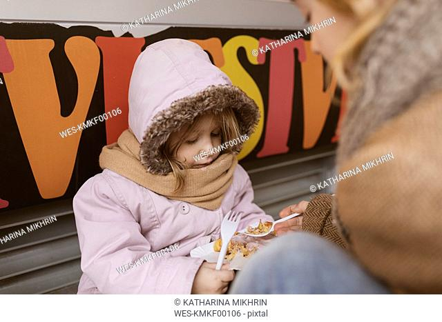 Belgium, little girl sharing Belgian waffle with her brother in winter