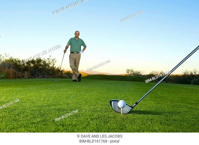 Caucasian man watching opponent tee off on golf course