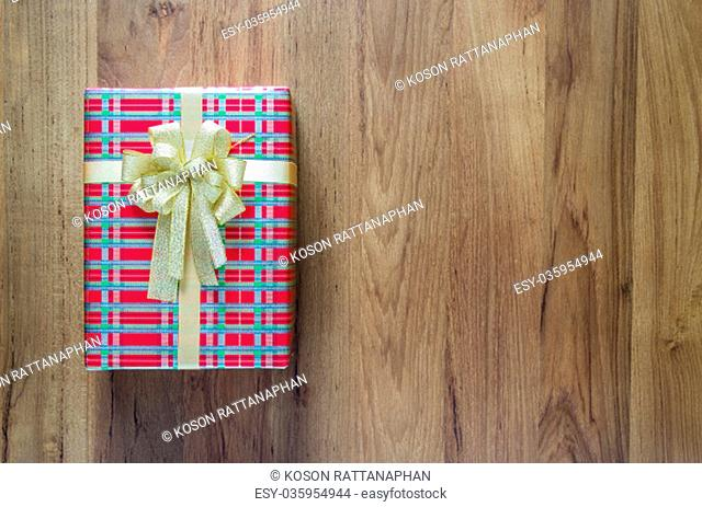 Christmas holidays and Happy New Year background. Gift boxes with red paper and golden ribbon on wooden table. Top view with copy space