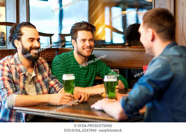 male friends drinking green beer at bar or pub