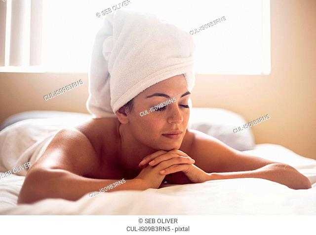 Serene young woman wrapped in towels lying on bed