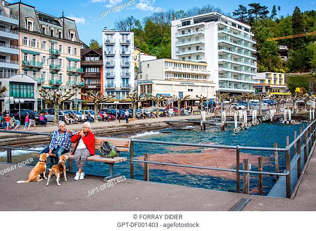 RETIRED COUPLE WITH THEIR TWO DOGS ON THE BANKS OF LAKE LUCERNE IN BRUNNEN, CANTON OF SCHWYZ, CENTRAL SWITZERLAND
