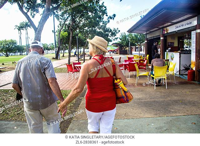 Older mature retired caucasian couple holding hands in the streets of Fort de France on a vacation. He wears a baseball hat and she a straw hat