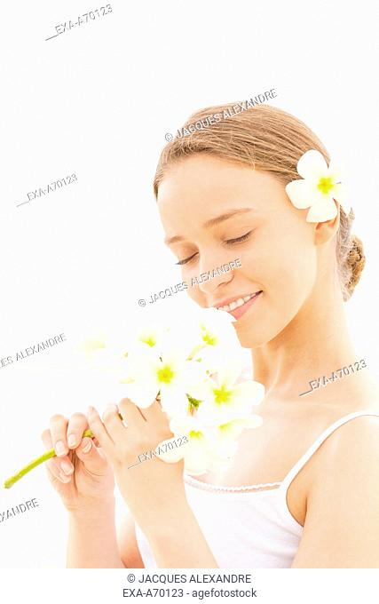 Woman smelling white orchid flower outdoors