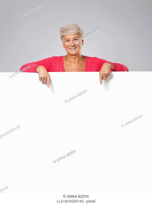 Lovely senior woman showing on empty whiteboard. Debica, Poland