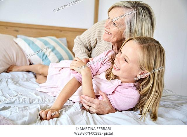 Little girl lying on the bed with her grandmother having fun