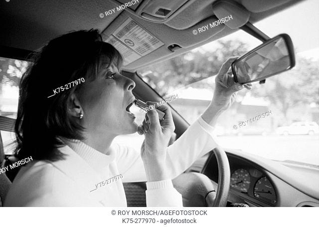 woman applying make-up in car