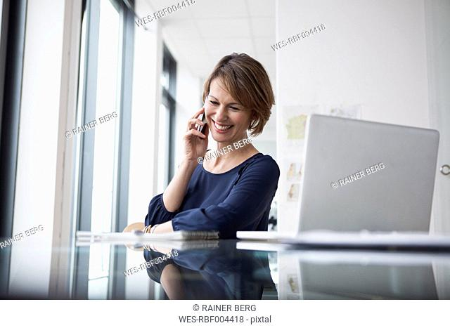 Smiling businesswoman on cell phone at office desk