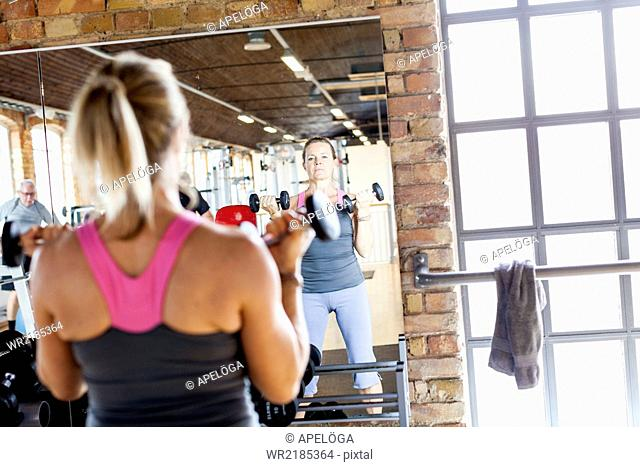 Mature woman lifting dumbbells in front of mirror at health club