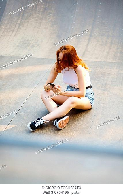 Redheaded woman using smartphone outdoors