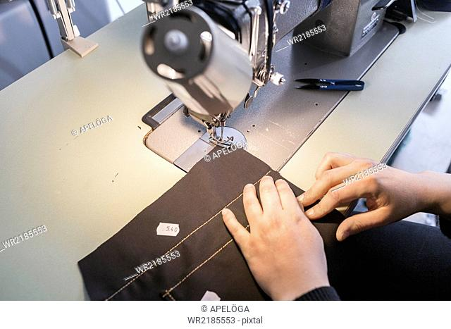 Female fashion designer using sewing machine in jeans factory