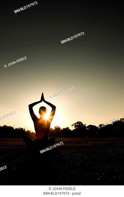 Caucasian woman practicing yoga at sunset