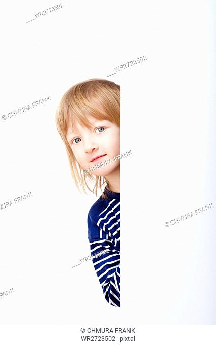 curious boy with long blond hair peeking out from behind a white board looking