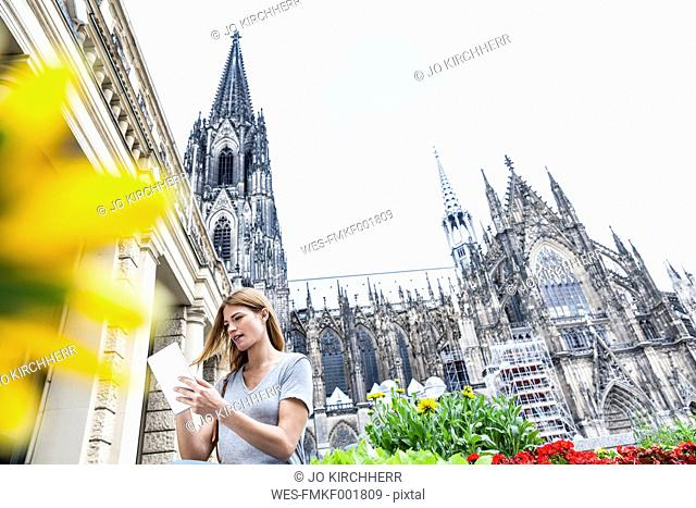 Germany, Cologne, young woman with digital tablet in front of Cologne Cathedral