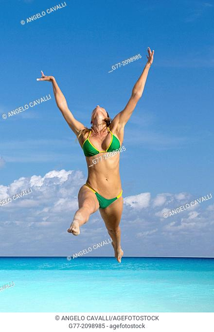 Young woman jumping on the beach, Miami Beach, Florida, USA