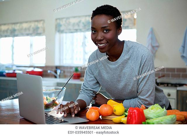 Portrait of beautiful woman learning food recipe from laptop