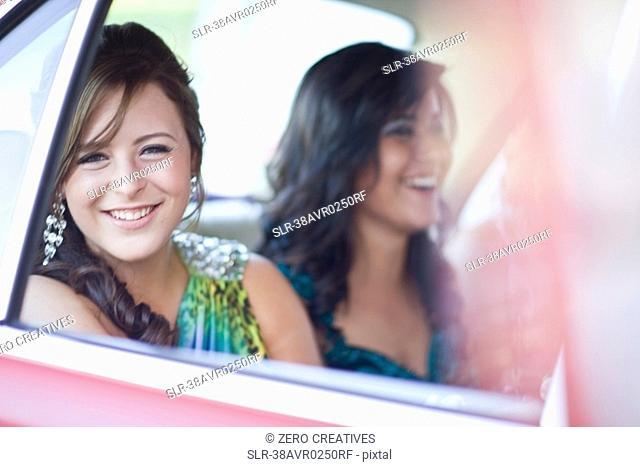 Teenage girl in gown sitting in car
