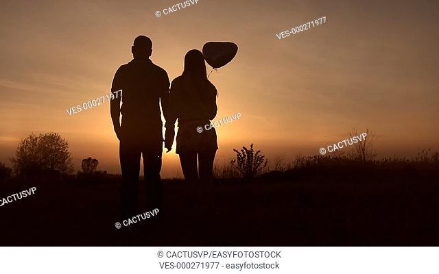 Romantic couple in love watching beautiful sunset