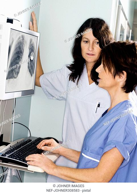A doctor and a nurse looking at a x-ray picture