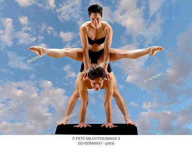 Mid adult dancers balancing on top of each other against blue sky