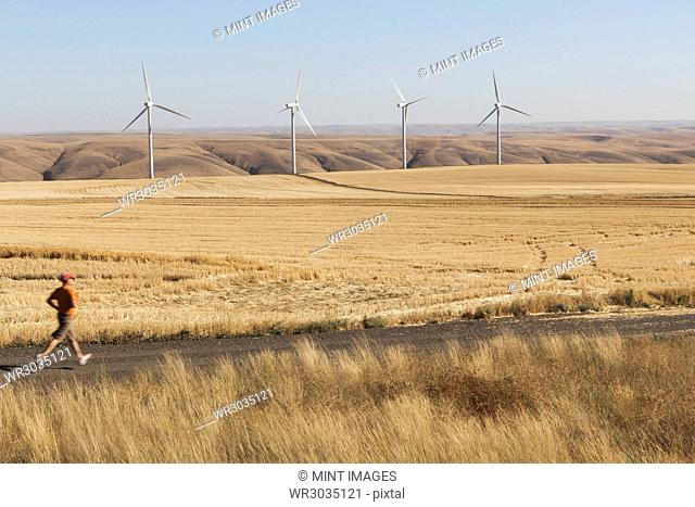 Man jogging on rural road, farmland and wind turbines in distance, Washington
