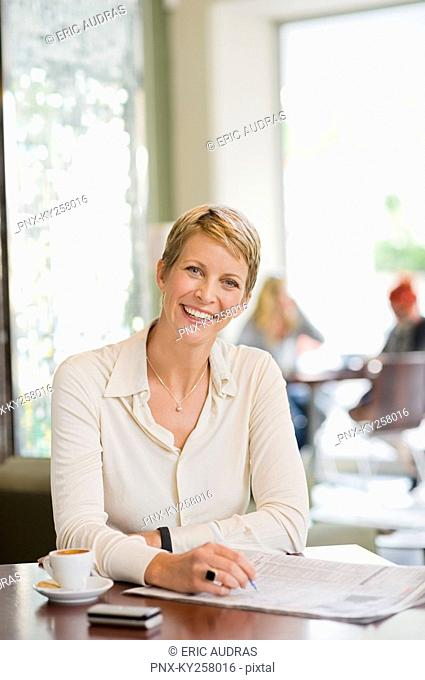 Businesswoman sitting in a restaurant and reading a financial newspaper