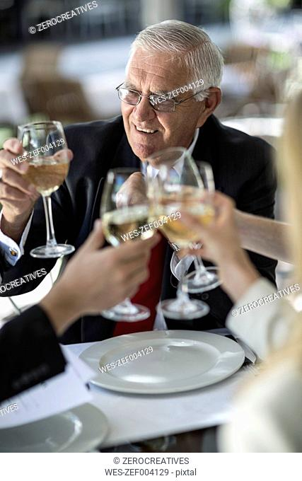 People at outside restaurant clinking white wine glasses