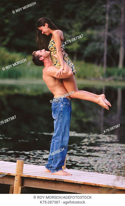 Healthy man lifts his girlfriend