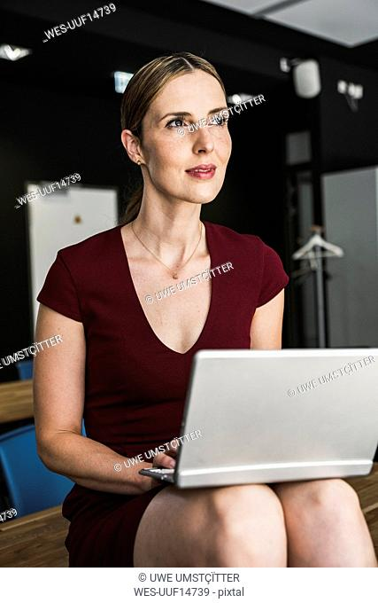 Businesswoman in office wearing burgundy dress using laptop