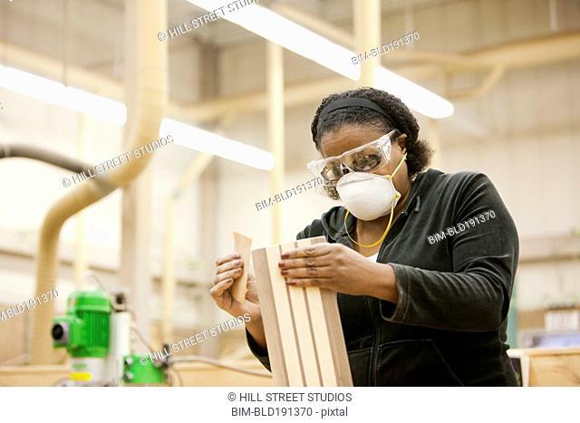 African woman sanding wood in workshop