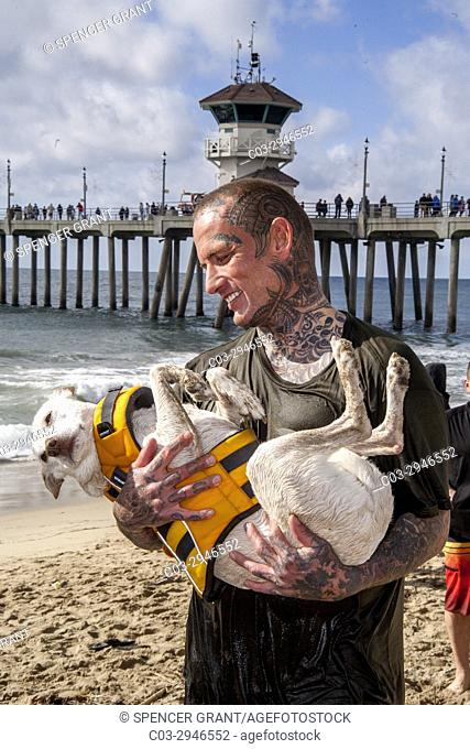 A dog in a life jacket gets a hug from his tattooed owner after braving the waves by the pier in Huntington Beach, CA. Note lifeguard station