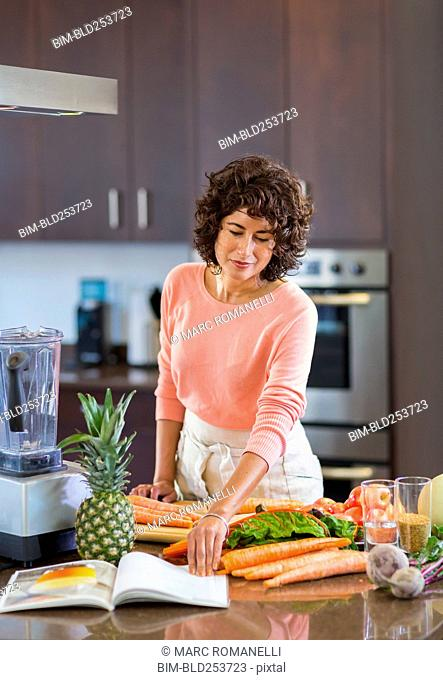 Hispanic woman reading cookbook