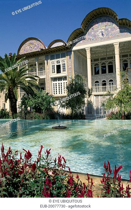 Ghajar Palace Kakh -E -Eram Garden of Paradise. Palace exterior seen from across a pool with flowers in the foreground