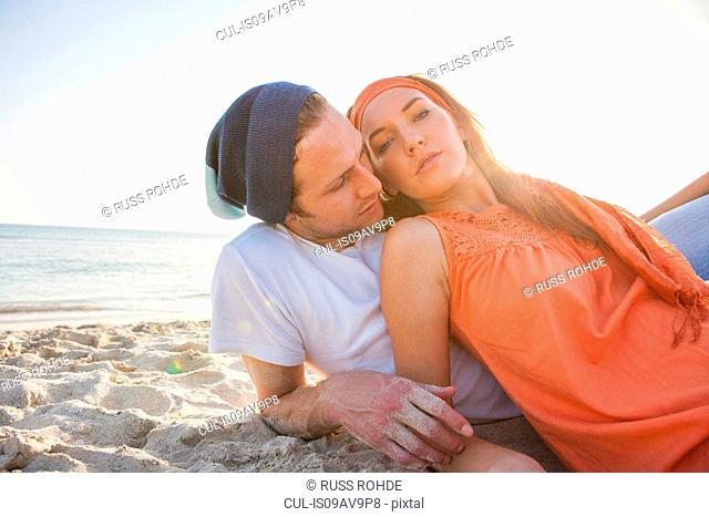 Portrait of romantic young couple reclining on beach, Majorca, Spain