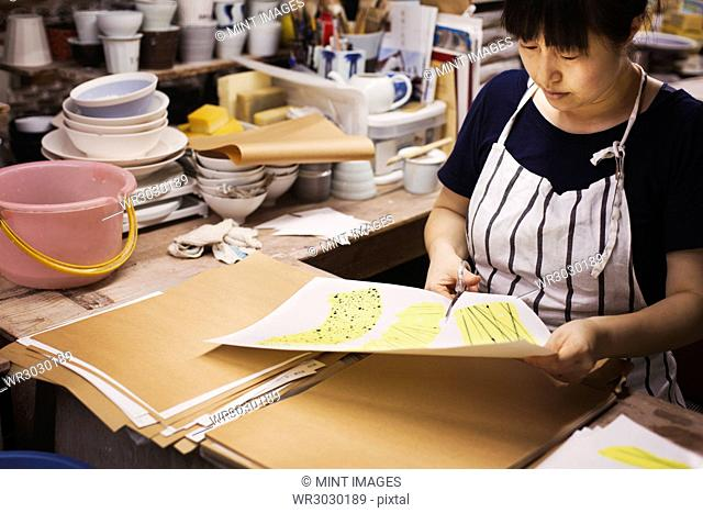 Woman sitting in a Japanese porcelain workshop, cutting out design patterns with a pair of scissors