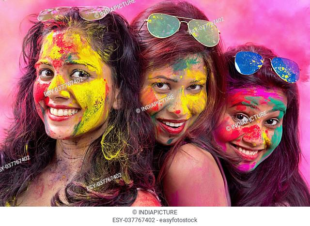 Portrait Of Three Young Indian Women With Colored Face celebrating Holi Color festival