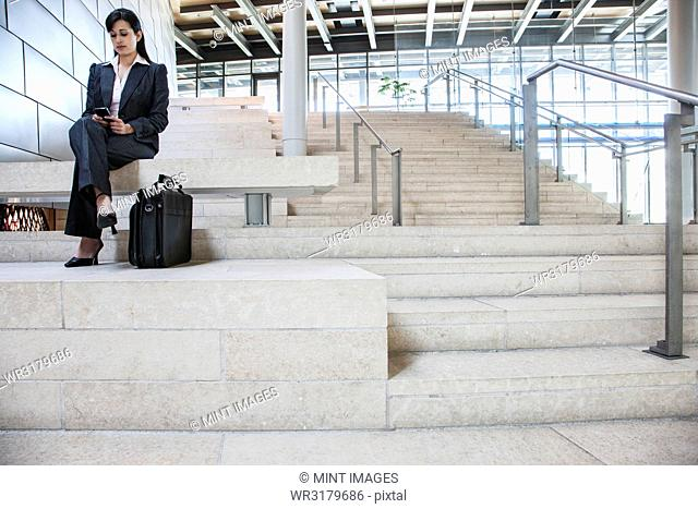 Hispanic businesswoman sitting on stairs in the lobby of a large office building