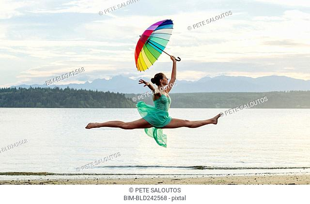 Caucasian ballerina jumping with multicolor umbrella on beach