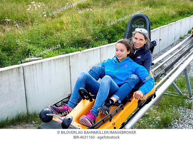 Mother and daughter enjoying a ride with the Alpine Coaster, summer toboggan run at the Kolbensattelhütte near Oberammergau, Upper Bavaria, Bavaria, Germany