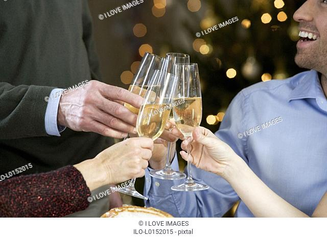 A family celebrating Christmas with a glass of champagne