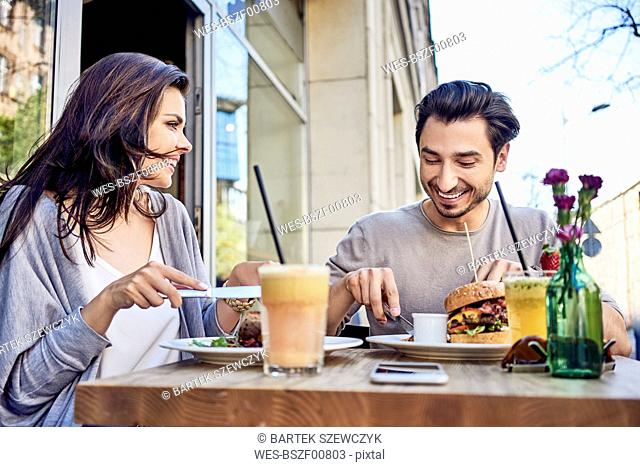 Happy young couple having lunch at outdoors restaurant