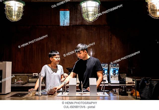 Two male baristas at counter in independent coffee roaster and cafe, Bangkok
