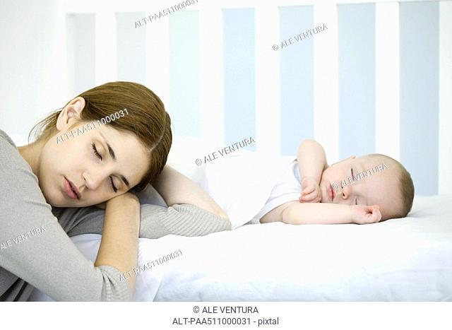 Mother resting head beside sleeping infant, eyes closed
