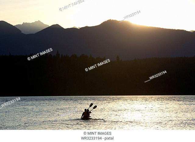 A couple sitting in a sit-on- top Kayak paddling in Puget Sound near the Olympic Mountains in Washington State, USA