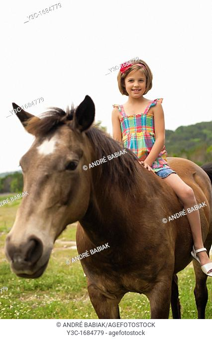 Young girl sitting on horseback attempting to ride a horse