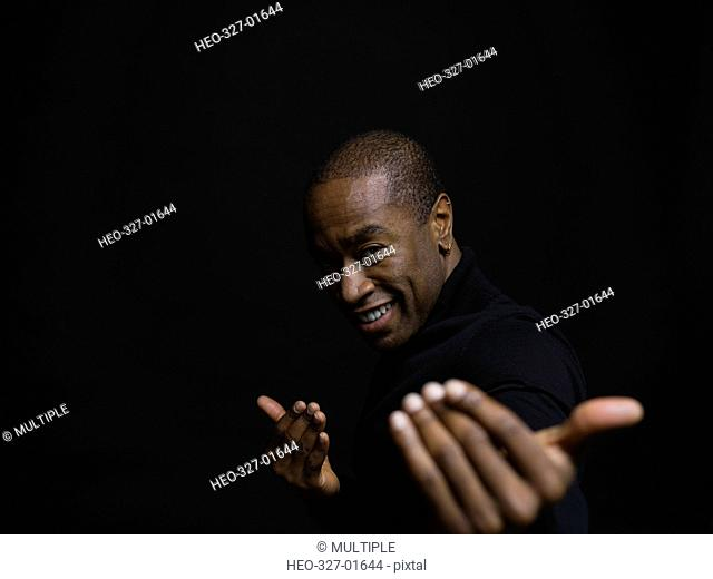 Portrait playful African American man gesturing against black background