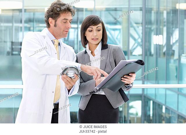 Engineer in lab coat and businesswoman holding part and folder in office