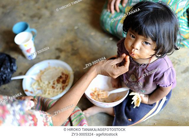 A maya indigenous girl is fed lunch provided by local NPO in Aqua Escondida, Solola, Guatemala